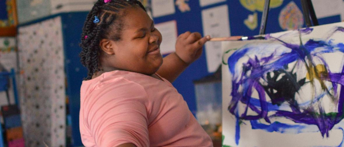An african american young woman paints with a smile on her face