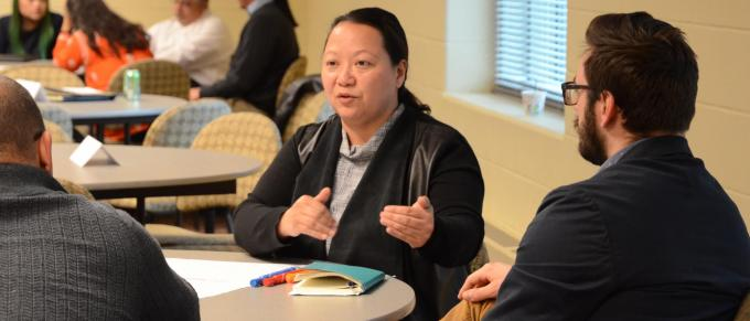 A Hmong woman speaks at a table
