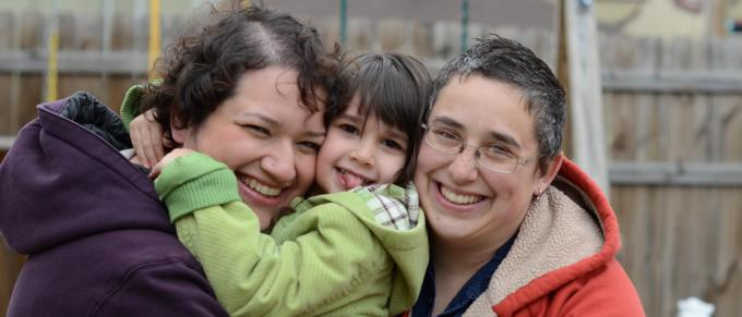 two women hug their young daughter